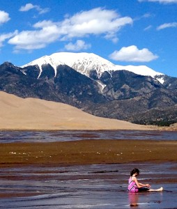 Kids and adults play in the shallow creek before crossing to hike up the dunes.