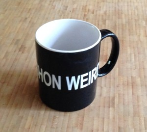 KEEP VASHON WEIRD, it says. But how do you take a rectangular  photo of a the lettering on a curved cup?