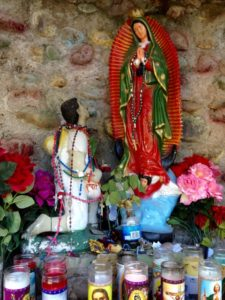 An altar with a pilgrim supplicating the Virgin, on the grounds around the Sanctuario.