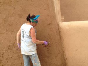 A local woman applying fresh mud on the walls.